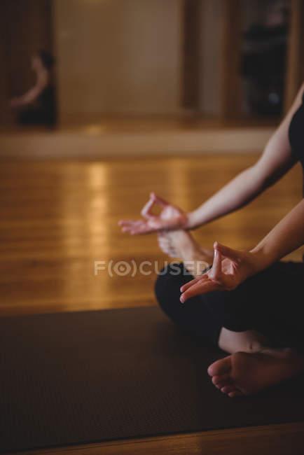 Обрезанное мнению практикующих женщины делают мудра на коврик йога в фитнес-студии — стоковое фото