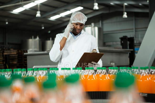 Работник мужского пола разговаривает по телефону во время осмотра продукции на заводе — стоковое фото