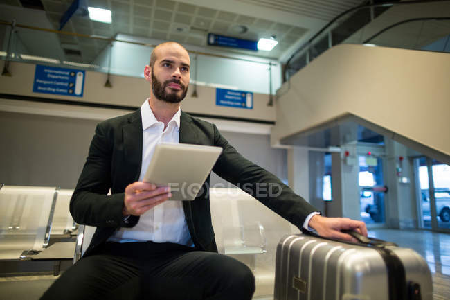 Businessman using digital tablet at airport — Stock Photo