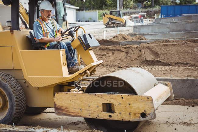 Людина, що діють дорожній каток на будівельний майданчик — стокове фото