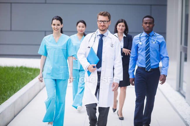 Equipo de médicos caminando en fila en los locales del hospital - foto de stock