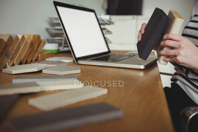 Mid section of business executive holding stone slabs in office — Stock Photo