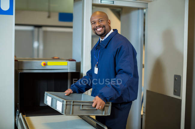 Portrait of smiling airport security officer holding a crate near conveyor belt at airport terminal — Stock Photo