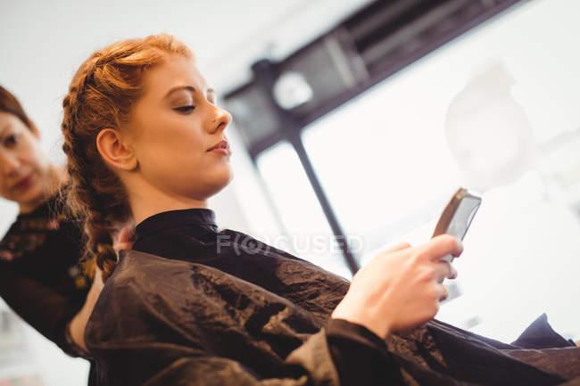 Красивая женщина с помощью мобильного телефона в салоне — стоковое фото