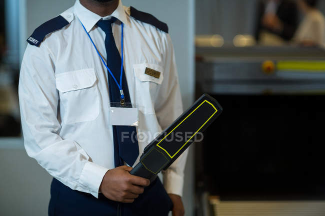 Середине секции сотрудник безопасности аэропорта, холдинг металлоискатель в аэропорту терминал — стоковое фото
