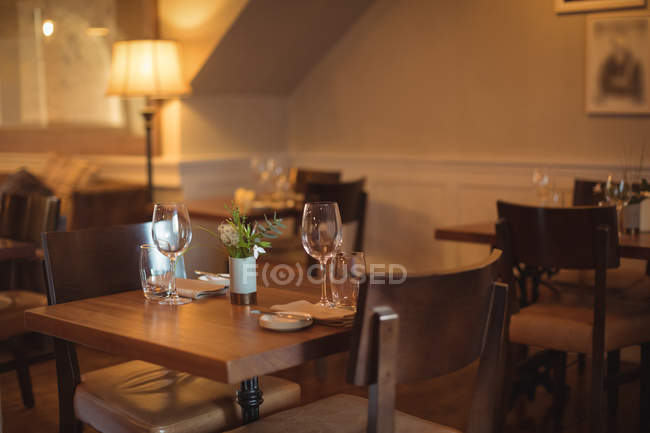 Tables and chairs arranged in empty modern coffee shop — Stock Photo