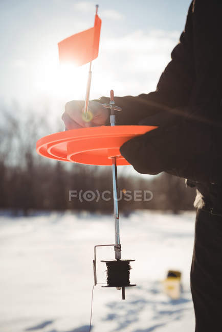 Mid section of ice fisherman setting up spinning reel in snowy landscape — Stock Photo