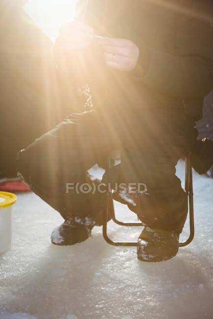 Seção intermediária de pescador de gelo, sentado na cadeira em barraca na luz suave — Fotografia de Stock