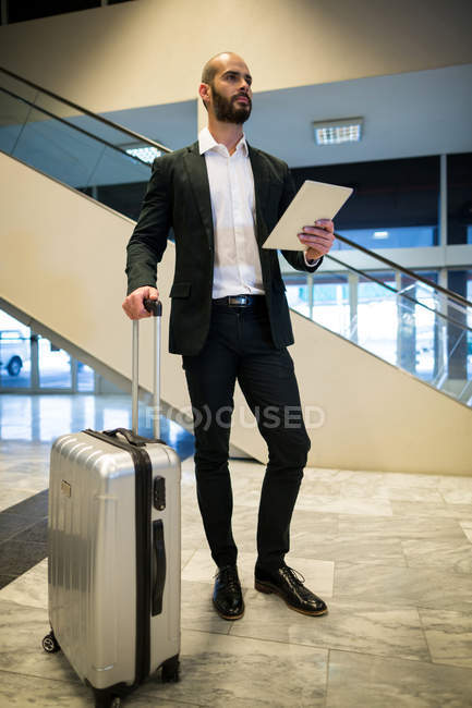 Businessman standing with luggage using digital tablet in waiting area at airport terminal — Stock Photo