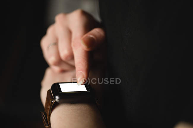 Mid-section of woman using smart watch at home — Stock Photo