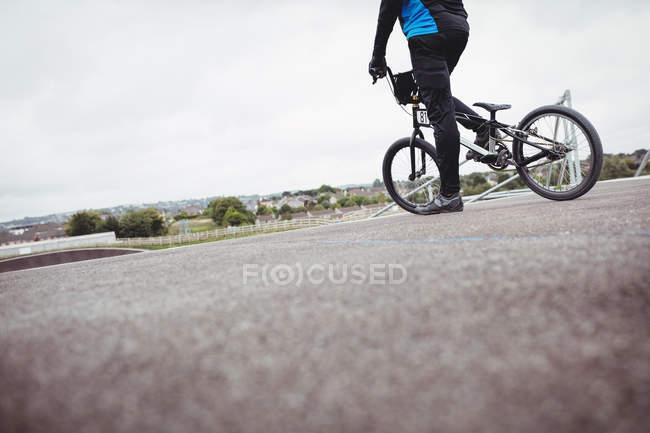 Велосипедист, стоящий на велосипеде BMX на старте пандуса в скейтпарке — стоковое фото