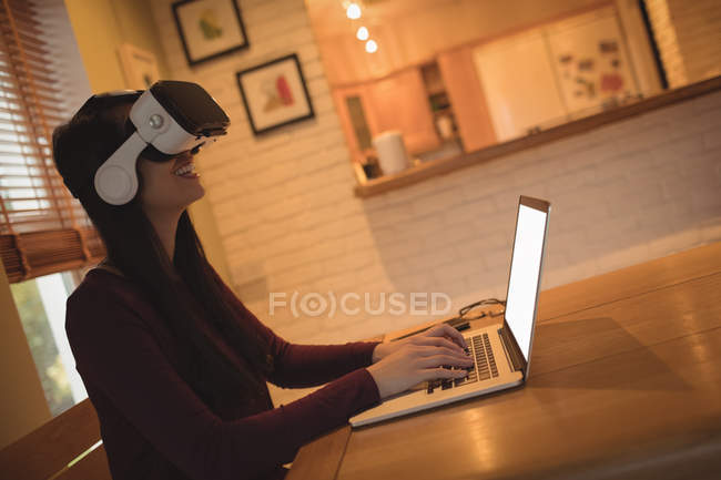 Woman using virtual reality headset while typing on laptop at home — Stock Photo