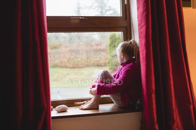 Ragazza premurosa seduta sul davanzale della finestra a casa — Foto stock
