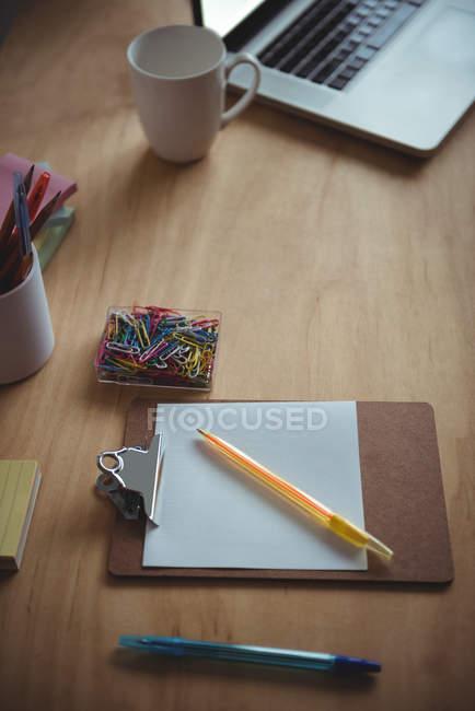 Accesorios de oficina y taza de café con el portátil sobre la mesa en la oficina - foto de stock