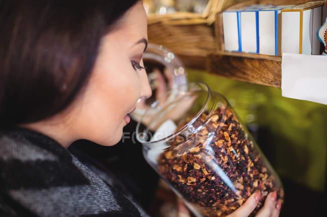 Gros plan de belle femme sentant pot d'épices dans la boutique — Photo de stock