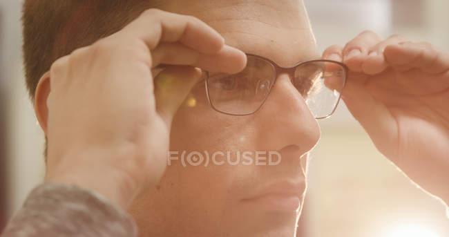 Крупный план мужчины в очках в магазине оптики — стоковое фото