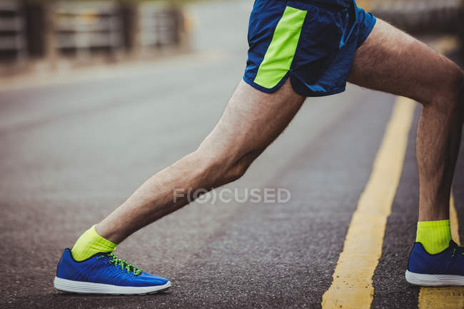 Low section of athlete performing stretching exercise on road — Stock Photo
