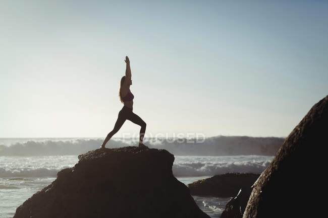 Woman performing yoga on rock at dusk — Stock Photo