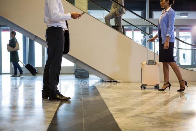 Пассажиры, идущие в терминале аэропорта с багажом в аэропорту — стоковое фото