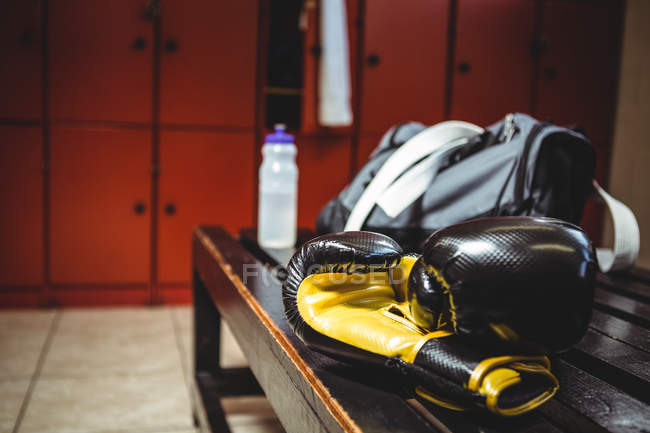 Close-up of boxing gloves on bench in locker room — Stock Photo