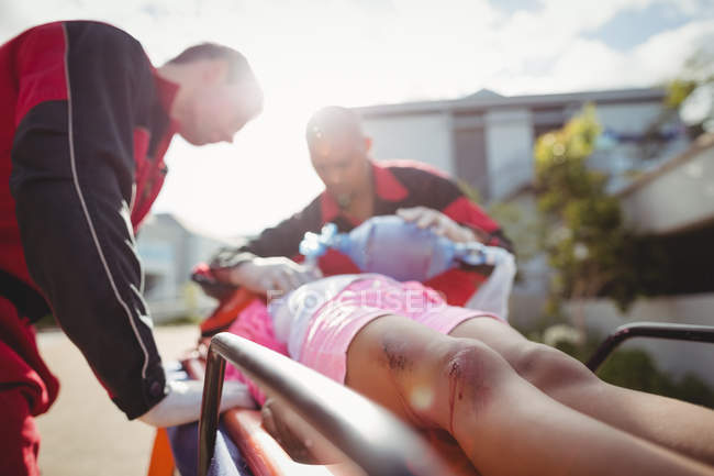 Paramédico dando oxigênio para menina ferida no local do acidente — Fotografia de Stock