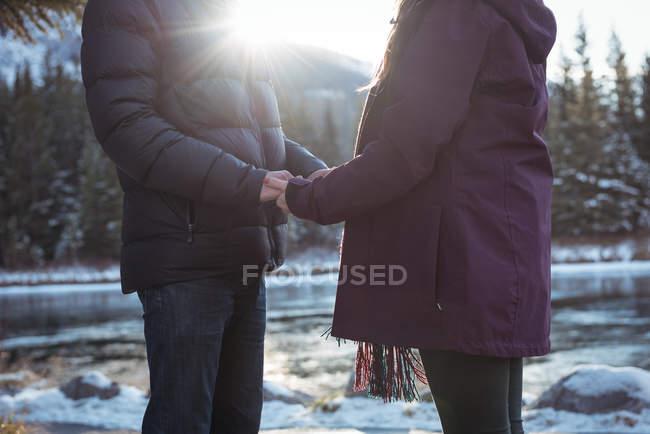 Sección media de pareja romántica parada junto al río en invierno - foto de stock
