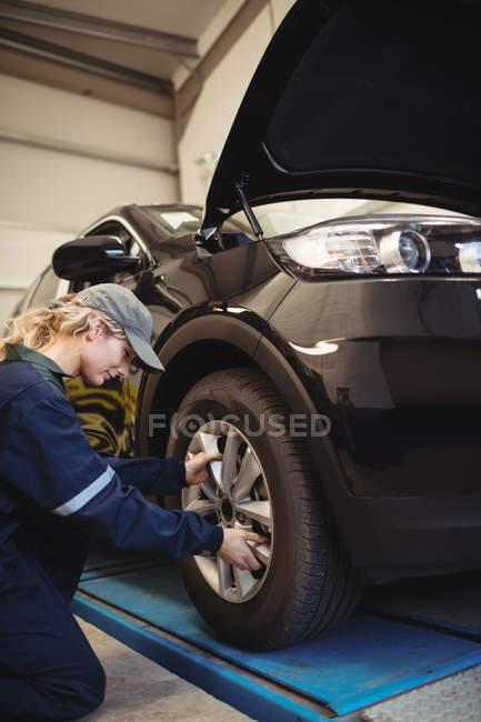 Meccanico donna esaminando una ruota di auto in garage di riparazione — Foto stock