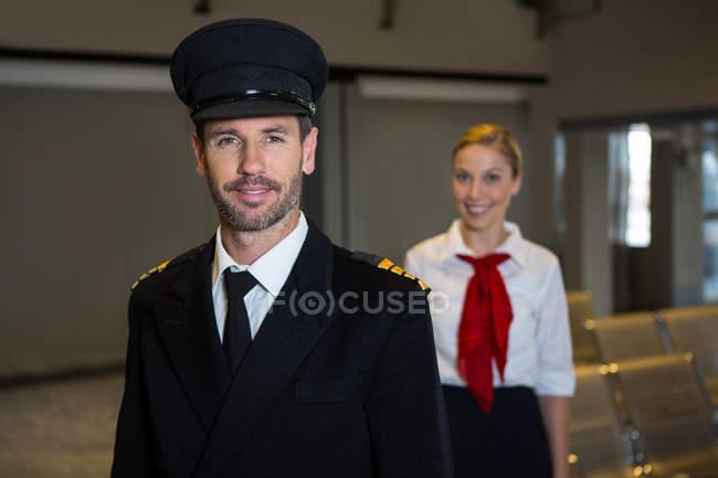Retrato de feliz piloto e aeromoça de pé no terminal do aeroporto — Fotografia de Stock
