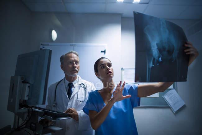 Врач и медсестра осматривают рентген в больнице — стоковое фото