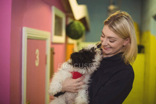 Cheerful woman carrying papillon dog at dog care center — Stock Photo
