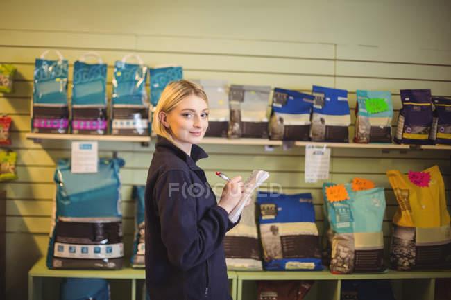 Retrato de mulher escrevendo no bloco de notas em loja no centro de cuidado do cão — Fotografia de Stock