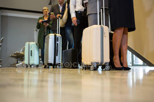 Низкий сегмент пассажиров с тележками, стоящими в очереди — стоковое фото