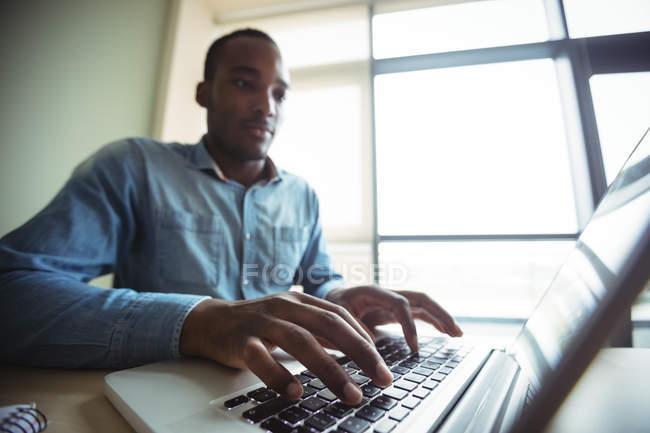 Business executive utilizzando laptop in ufficio — Foto stock