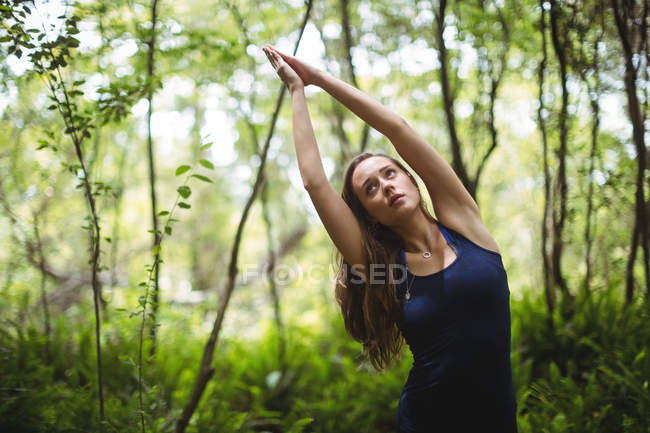 Woman performing yoga in forest on a sunny day — Stock Photo