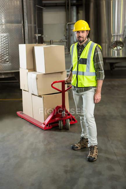 Portrait complet d'un ouvrier tirant un chariot dans un entrepôt — Photo de stock