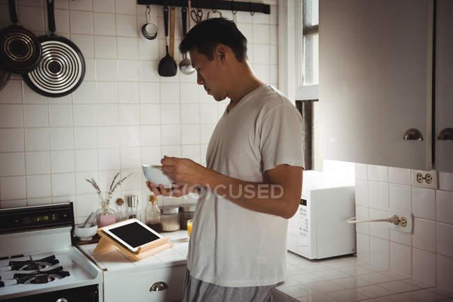 Homme prenant le petit déjeuner tout en regardant tablette numérique dans la cuisine à la maison — Photo de stock