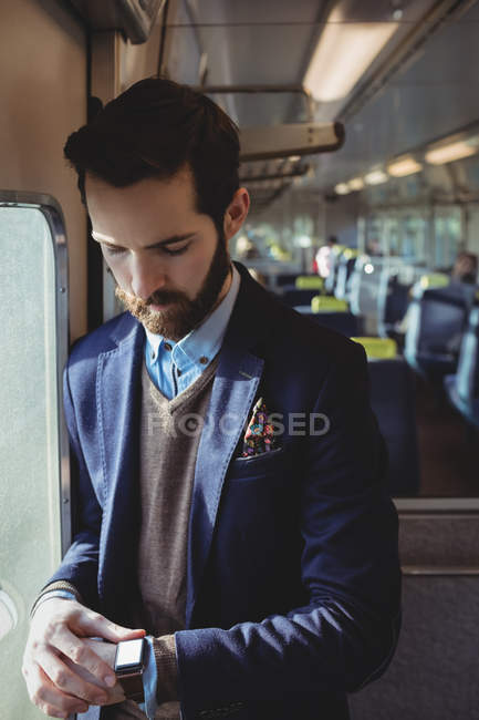 Businessman checking time on smartwatch while travelling in train — Stock Photo