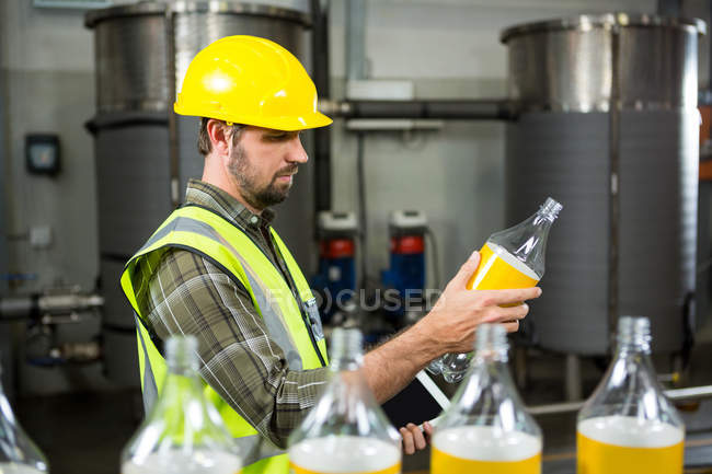 Side view of serious male worker inspecting bottles in juice factory — Stock Photo