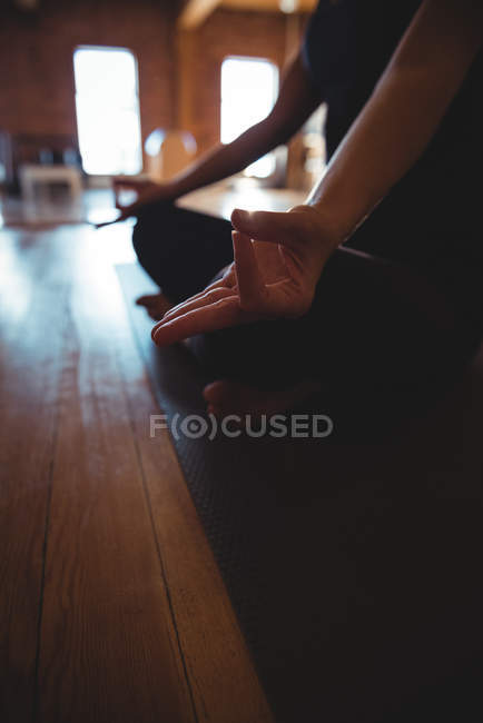 Cropped view of meditating woman doing mudra on mat in yoga studio — Stock Photo