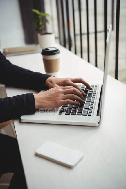 Mano dell'uomo che utilizza il computer portatile in caffetteria — Foto stock