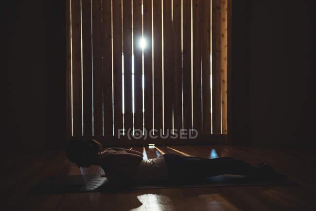 Mujer practicando yoga en la gimnasio oscuro con retroiluminado - foto de stock