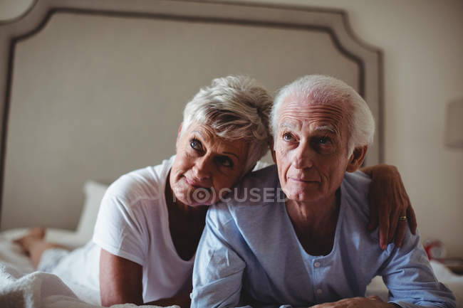 Happy senior couple lying on bed in bed room — Stock Photo