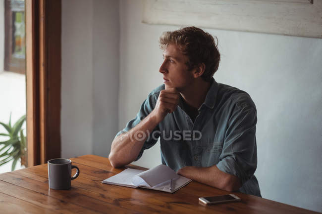 Thoughtful man sitting desk with notebook and coffee cup at home — Stock Photo