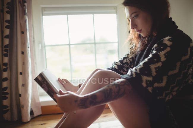 Woman sitting near window and reading a book at home — Stock Photo