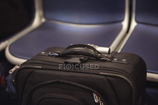 Gros plan du sac de voyage trolley de couleur noire contre les sièges de transport — Photo de stock
