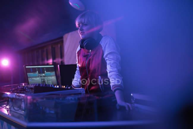 Bastante hembra dj jugando música en el bar - foto de stock