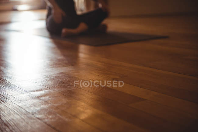 Close-up of wooden flooring in fitness studio and practicing person in background — Stock Photo