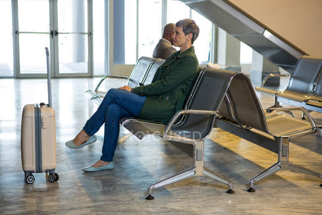 Woman sitting with luggage at waiting area in airport terminal — Stock Photo