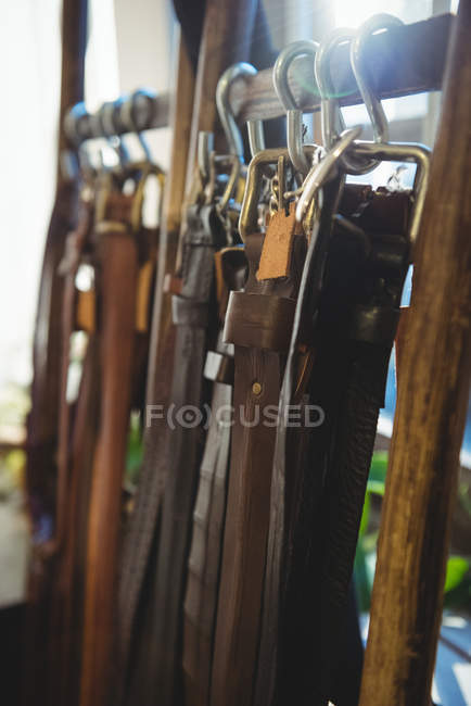 Various leather accessories hanging on hooks in workshop — Stock Photo