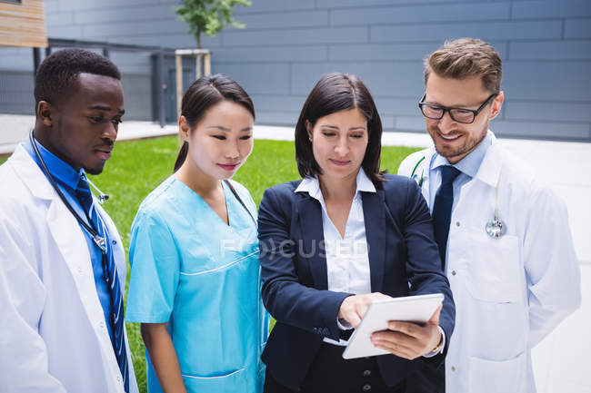 Team of doctors discussing over digital tablet in hospital premises — Stock Photo
